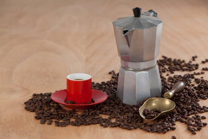 Granos de café, café, cafetera y cucharada foto de archivo
