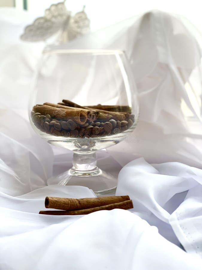 Granos de café con canela en un vidrio Colores de Brown en un fondo blanco fotos de archivo
