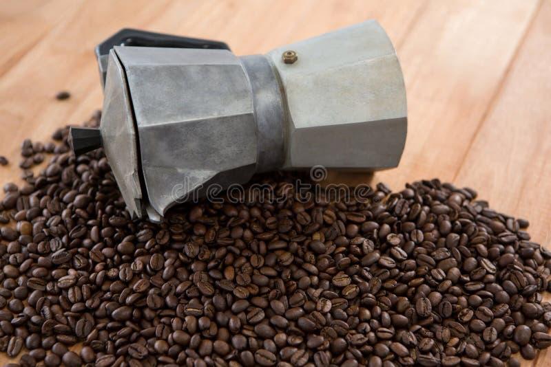 Granos de café con la cafetera metálica imágenes de archivo libres de regalías