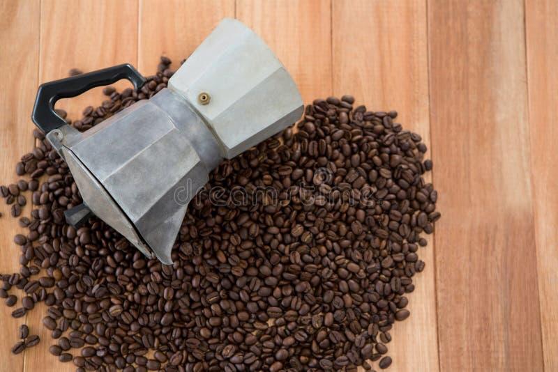 Granos de café con la cafetera metálica imagen de archivo