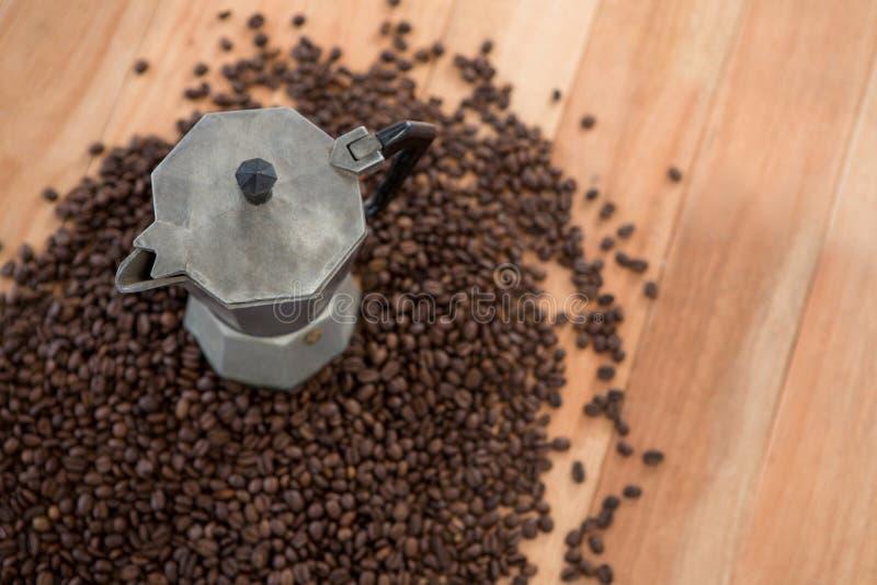 Granos de café con la cafetera metálica foto de archivo
