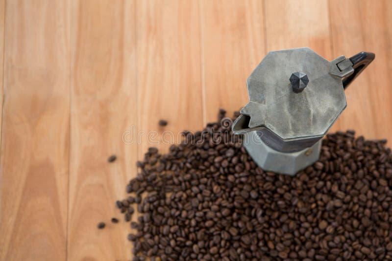 Granos de café con la cafetera metálica fotografía de archivo