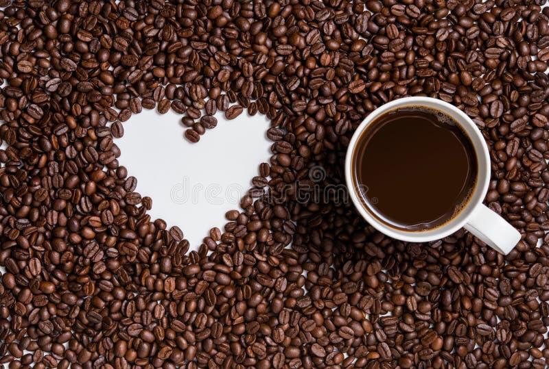Granos de café con la taza de café foto de archivo