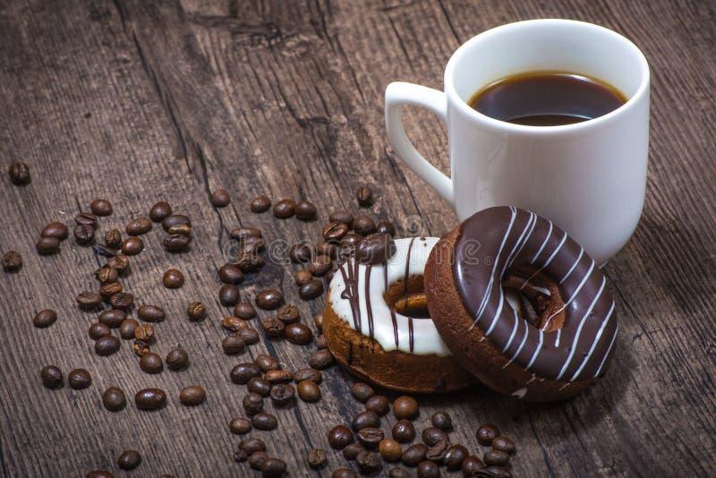 Granos de café con la taza de café y de anillos de espuma foto de archivo