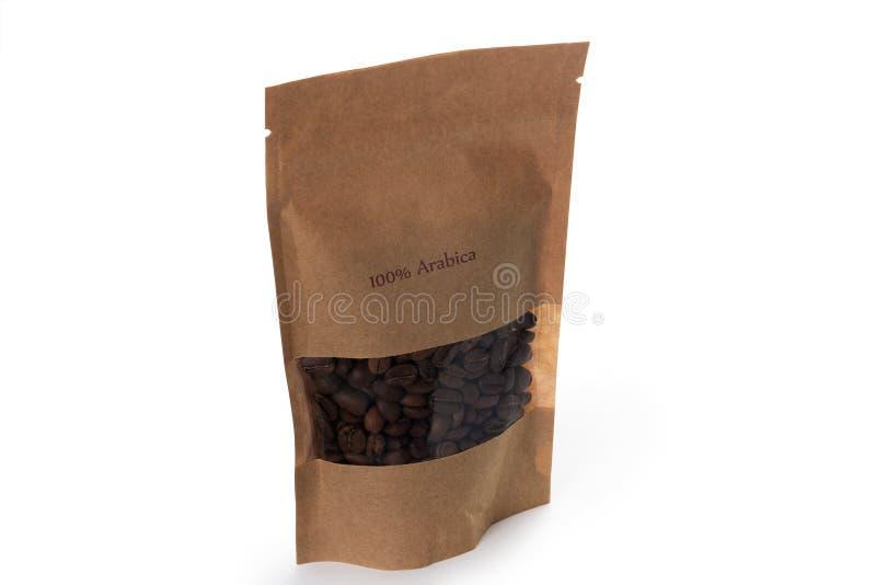 Granos de café de Brown en el paquete de papel imágenes de archivo libres de regalías