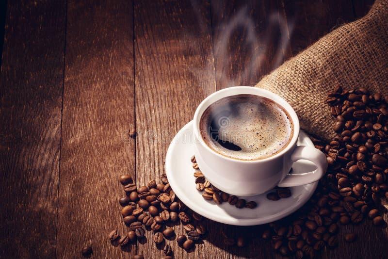 Granos de café de la taza de madera foto de archivo
