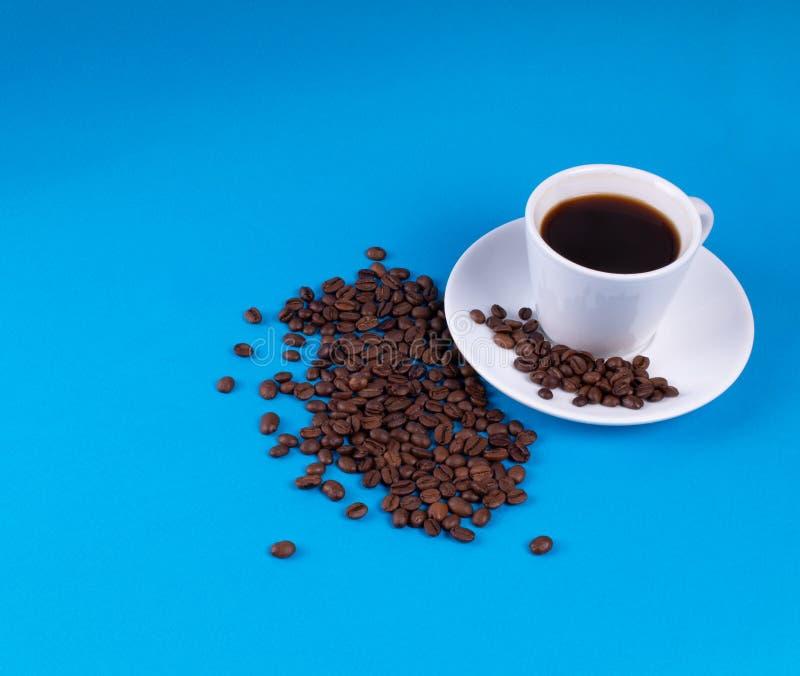 Granos de café derramados después de la taza blanca en fondo azul imágenes de archivo libres de regalías