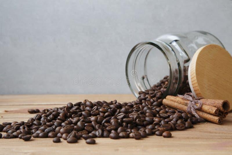 Granos de café derramados hacia fuera de cristal poco tarro imagen de archivo