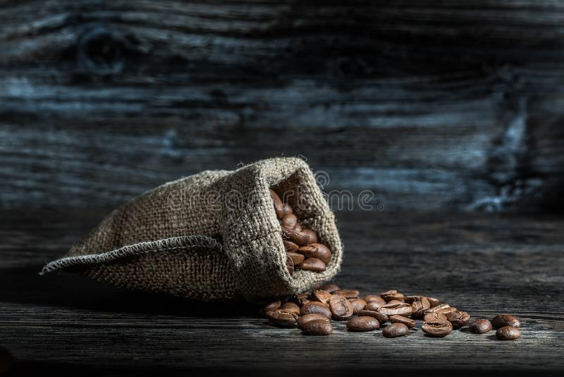 Granos de café dispersados del saco fotografía de archivo libre de regalías