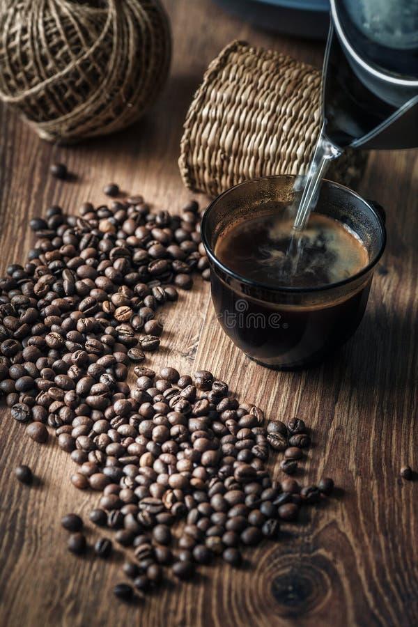 Granos de café dispersados en una tabla de madera y una taza de bebida vertidas en luz de la mañana fotos de archivo