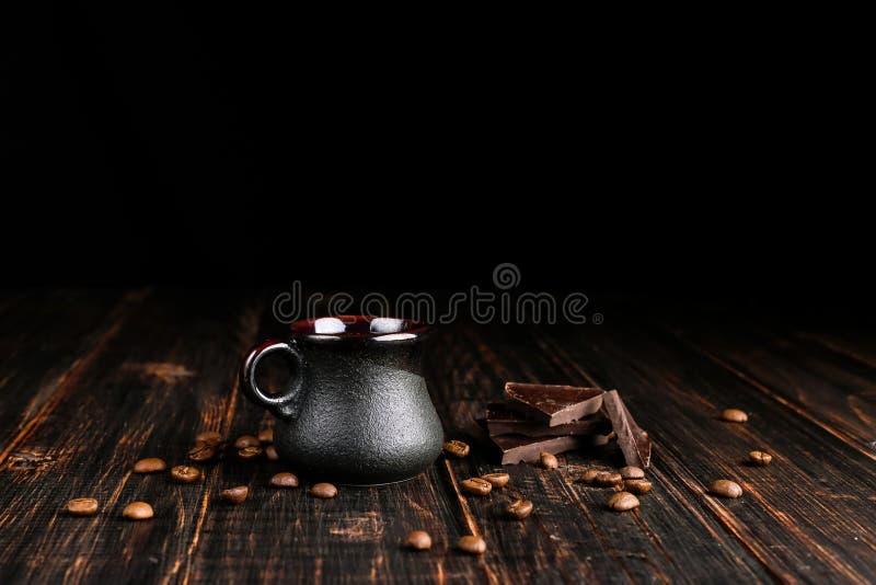 Granos de café dispersados, una taza y chocolate negro en una tabla de madera fotos de archivo