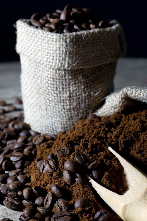 Granos de café en bolso del yute y el café molido con el primer de madera de la cucharada en negro fotos de archivo libres de regalías