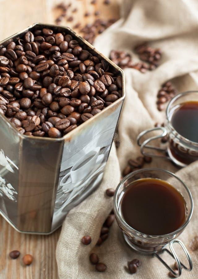 Granos de café en caja del metal y tazas de café viejas fotos de archivo libres de regalías
