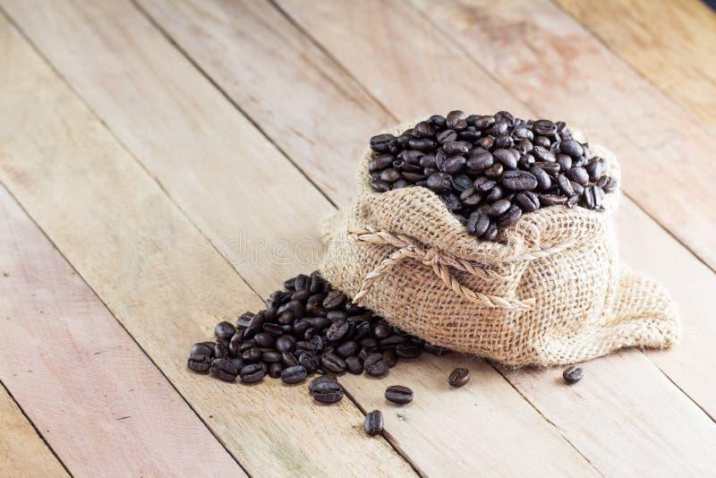 Granos de café en el bolso de café hecho de la arpillera en superficie de madera imagen de archivo