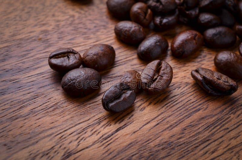 Granos de café en el fondo de madera imagen de archivo