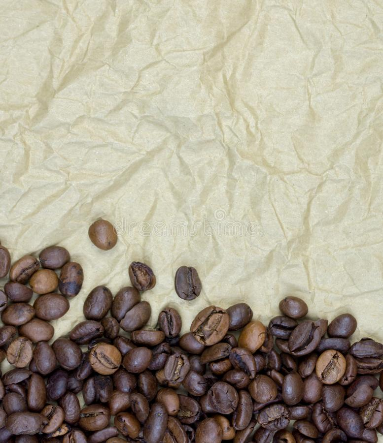 Granos de café en el papel de pergamino arrugado viejo, vertical imagen de archivo libre de regalías