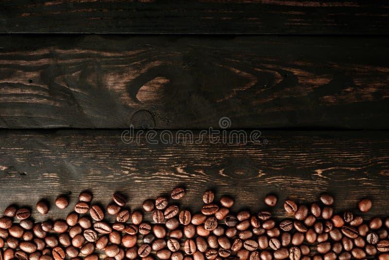 Granos de café en la madera del negro de la tabla imagen de archivo