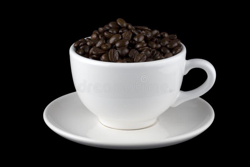 Granos de café en la taza blanca en el platillo imagen de archivo