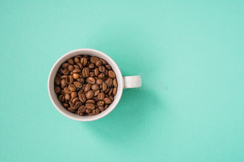 Granos de café en la taza blanca en una opinión superior del fondo de la turquesa imagen de archivo