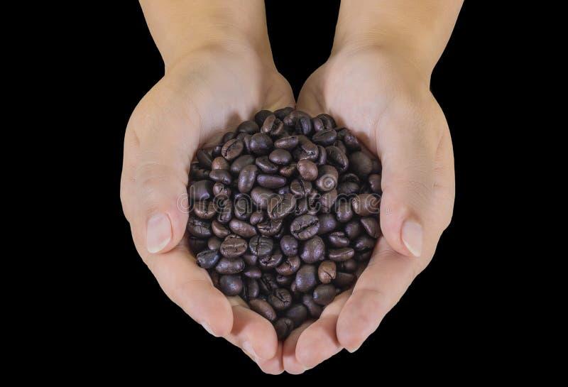 Granos de café en las manos masculinas en fondo negro fotos de archivo