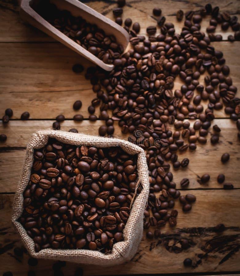 Granos de café en saco y cucharada del yute en el fondo de madera, visión superior fotos de archivo libres de regalías