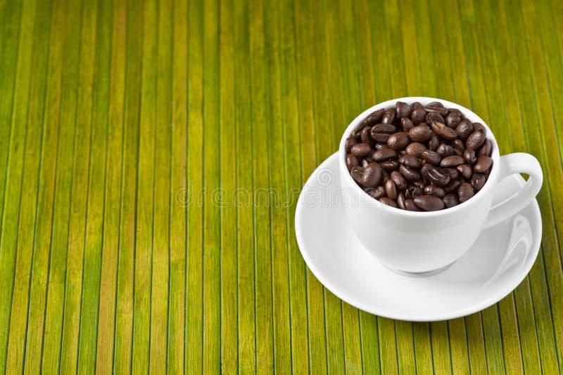 Granos de café en taza imagen de archivo