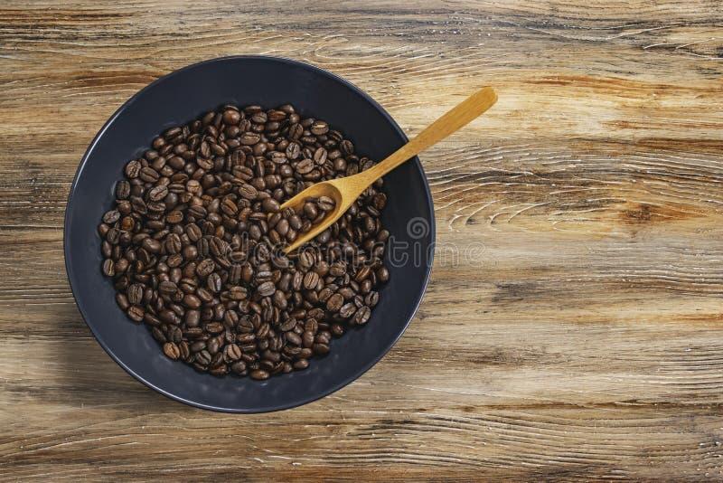 Granos de café en taza oscura del cuenco en fondo texturizado de madera aislado fotografía de archivo libre de regalías