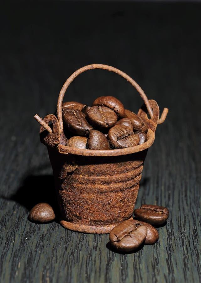 Granos de café en un pequeño cubo oxidado en un backgroun oscuro fotos de archivo
