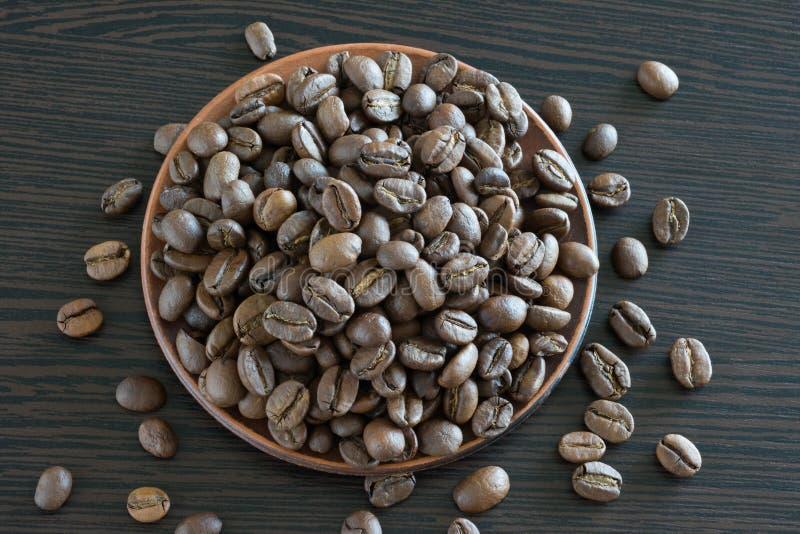 Granos de café en un plato por el primer y en una tabla de madera Clase desde arriba imagenes de archivo