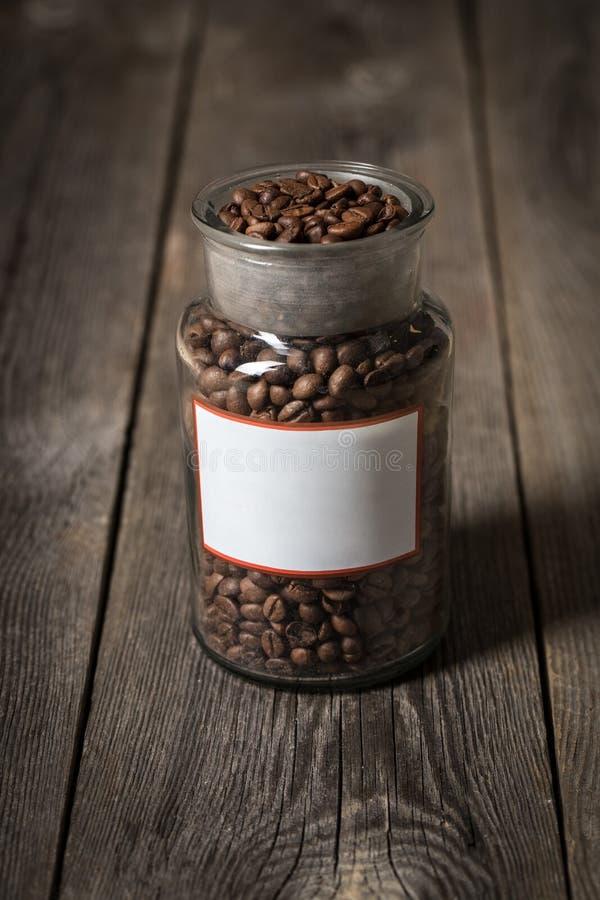 Granos de café en un tarro de cristal colocado en la tabla de madera fotos de archivo libres de regalías
