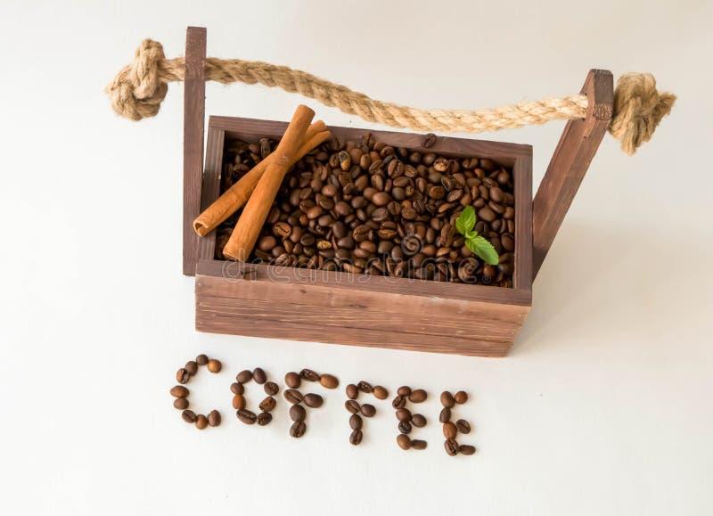Granos de café en una caja de madera, en un fondo blanco con canela fotos de archivo
