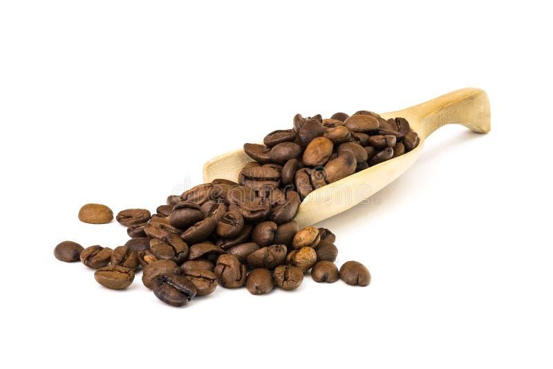 Granos de café en una cuchara de madera imagenes de archivo