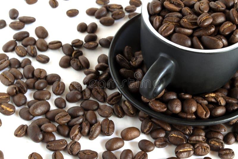 Granos de café en una pequeña taza foto de archivo libre de regalías