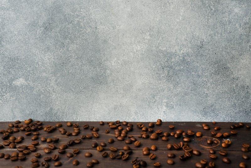 Granos de café en una tabla de madera Pared gris concreta con el espacio de la copia imágenes de archivo libres de regalías