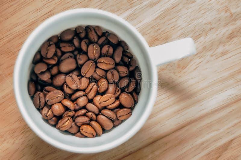 Granos de café en una taza blanca fotografía de archivo