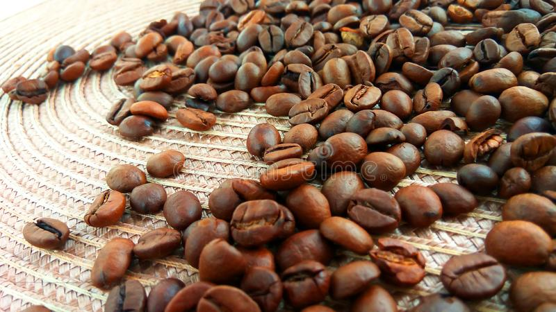 Granos de café marrones asados en fondo ligero del paño imagen de archivo libre de regalías