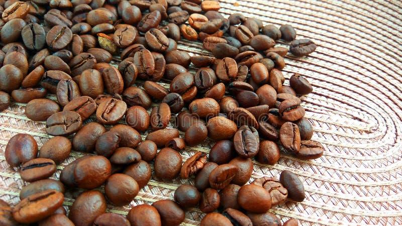 Granos de café marrones asados en fondo ligero del paño fotos de archivo libres de regalías