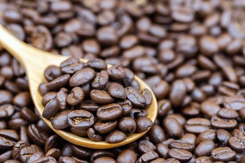 Granos de café marrones asados en la cuchara de madera imagenes de archivo