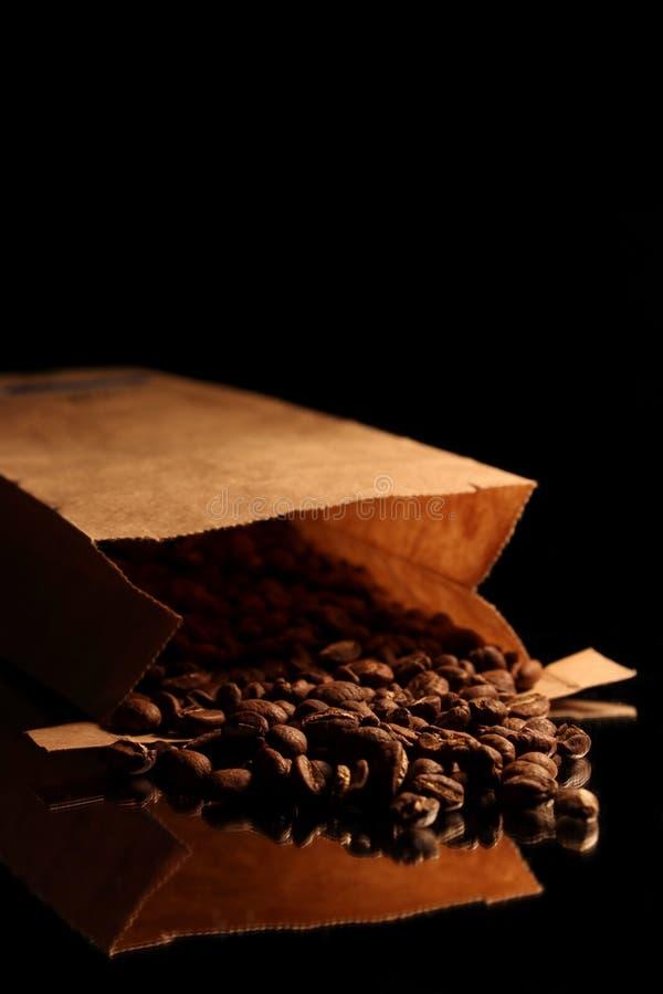 Granos de café que derraman hacia fuera la reflexión fotos de archivo