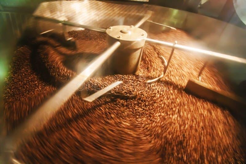 Granos de café recientemente asados en un tostador de café imagenes de archivo
