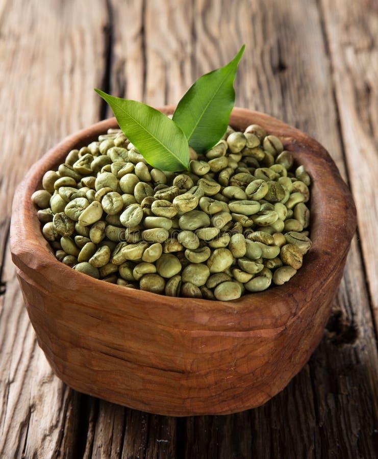 Granos de café verdes en tazón de fuente de madera foto de archivo libre de regalías