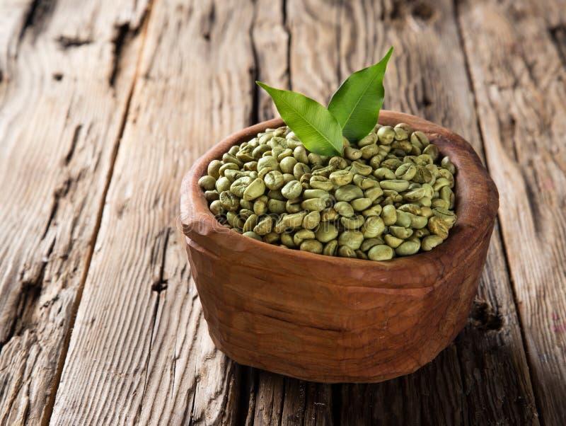 Granos de café verdes en tazón de fuente de madera foto de archivo