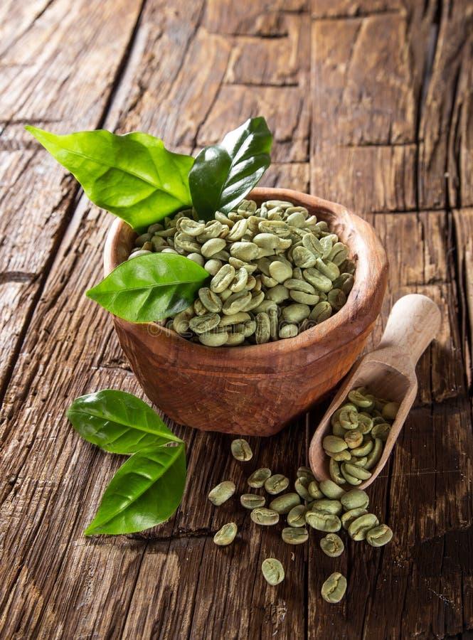 Granos de café verdes en tazón de fuente de madera fotos de archivo libres de regalías
