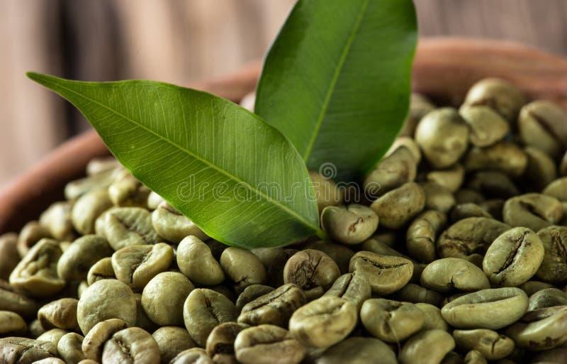 Granos de café verdes en tazón de fuente de madera imágenes de archivo libres de regalías