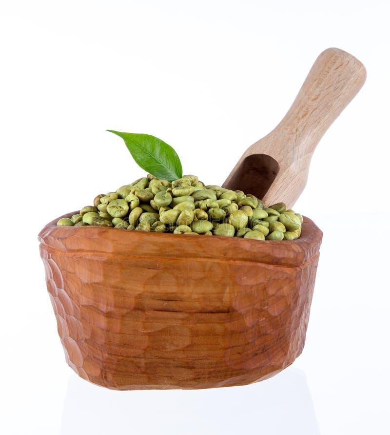 Granos de café verdes en tazón de fuente de madera fotos de archivo