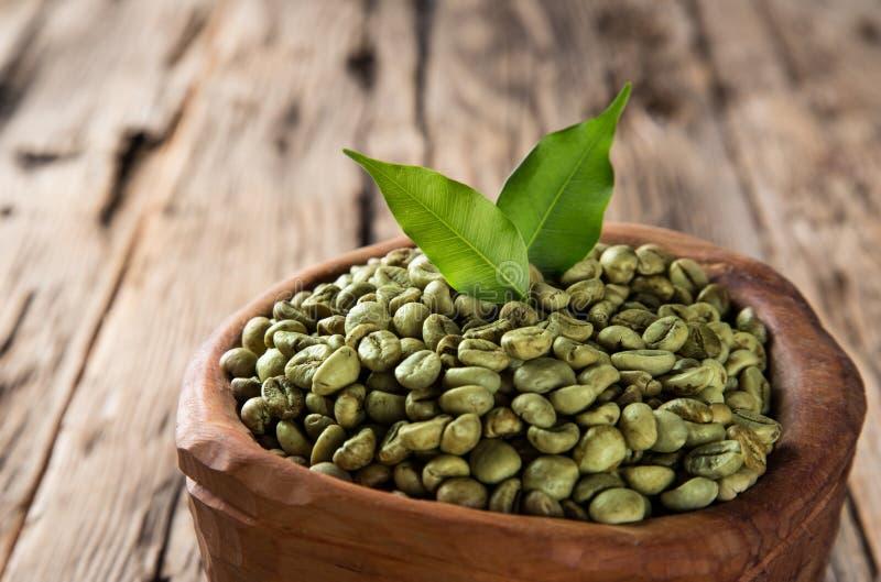 Granos de café verdes en tazón de fuente de madera fotografía de archivo libre de regalías