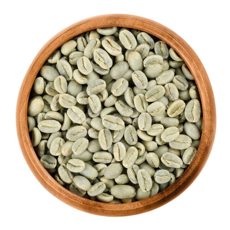 Granos de café verdes en un cuenco de madera sobre blanco fotos de archivo