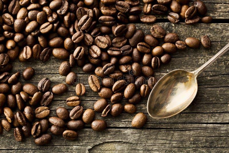 Granos de café y cuchara de plata foto de archivo libre de regalías