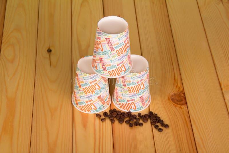 Granos de café y tres tazas vacías para el café, en la tabla imágenes de archivo libres de regalías