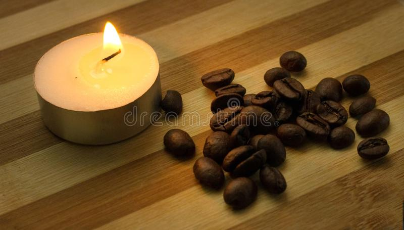 Granos de café y una vela encendida foto de archivo